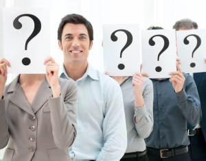 People holding question marks infront of their faces and one without