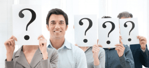 People holding large question marks, one man without