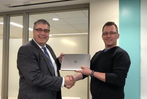 Hand shake with laptop, IT Infrastructure Manager, Jeremy Forstner, pictured right